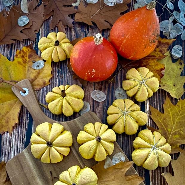 Kürbis und Kürbis-Brötchen auf Herbstlaub und  einem Holzbrett angerichtet