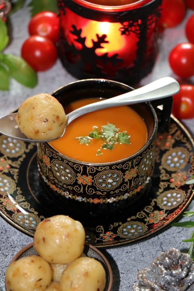 Eine Tasse Festliche Tomaten-Suppe , darauf ein liegender Löffel mit Kloß
