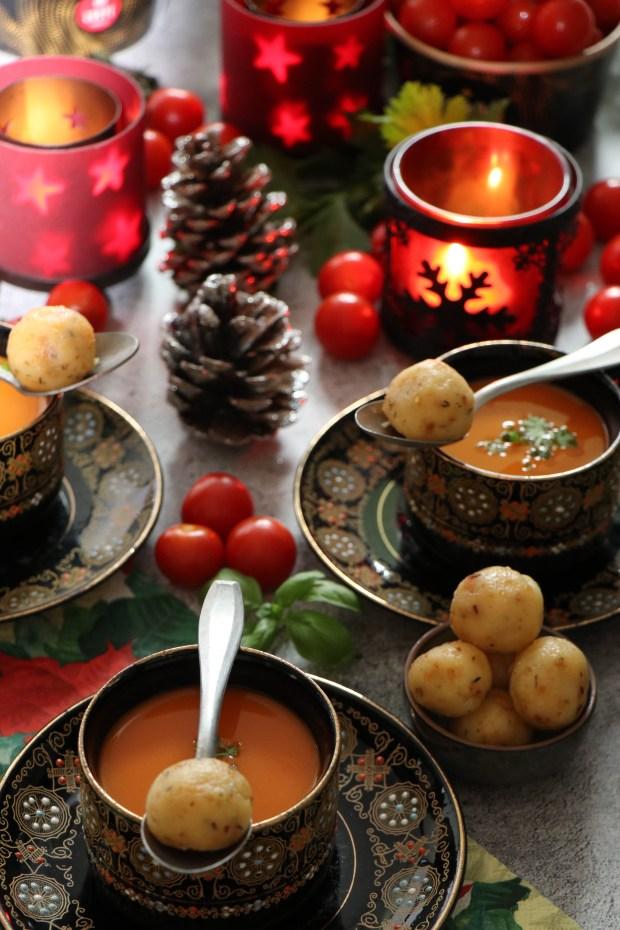 Weihnachtlich gedeckter Tisch mit drei Tassen Festliche Tomatensuppe in schwarzem Geschirr angerichtet