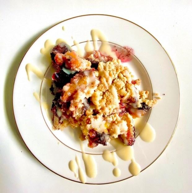 Zwetschgen-Crumble auf einem  cremefarbenen  Teller mit Goldrand  mit Vanillesauce angerichtet
