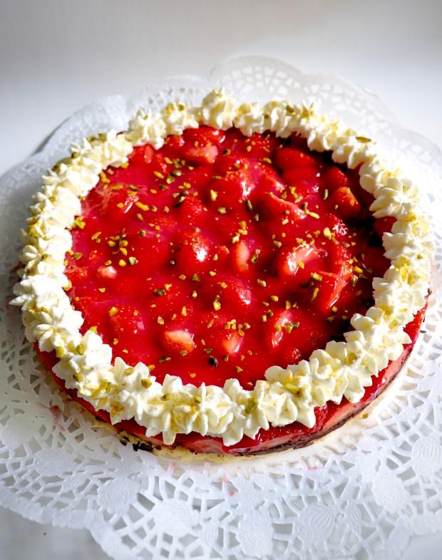 Erdbeer-Kuchen mit Schokoladen-Boden mit Schlagsahne und Pistazien garniert