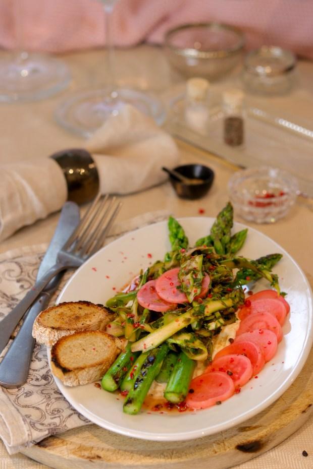 Eingelegte Radieschen mit grünem Spargel und gerösteten Brot auf einer ovalen Platte angerichtet.