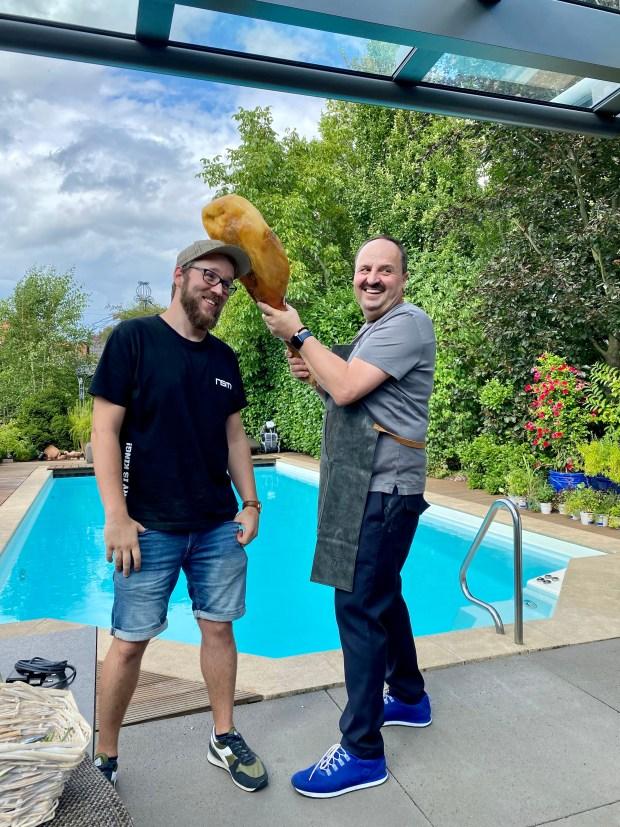 Johann Lafer bewaffnet mit einer Schinkenkeule und ein Mitarbeiter des Filmteams
