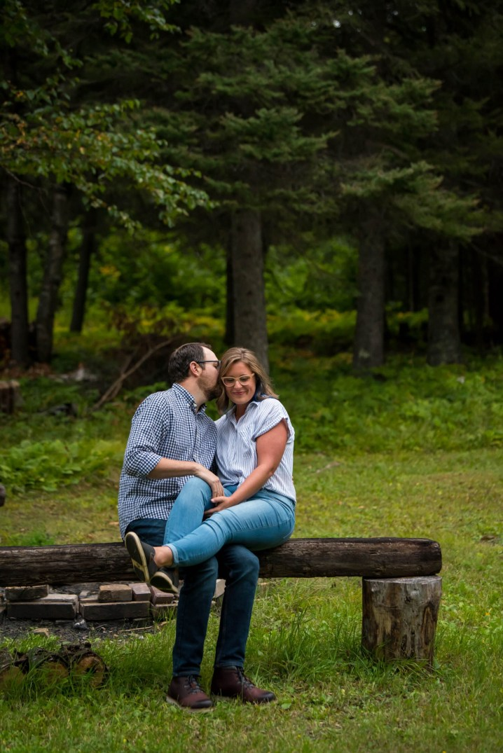 david dietz and lindsey lockett sitting on a wooden bench on a cloudy day. david is whispering in her ear and lindsey is laughing.