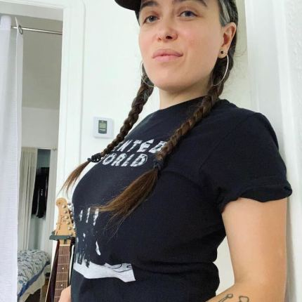 clementine morrigan wearing a hat with pigtail braids and a black shirt