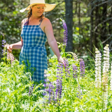 lindsey lockett standing in a patch of purple and white lupines. she is wearing a blue jumper and a floppy straw hat