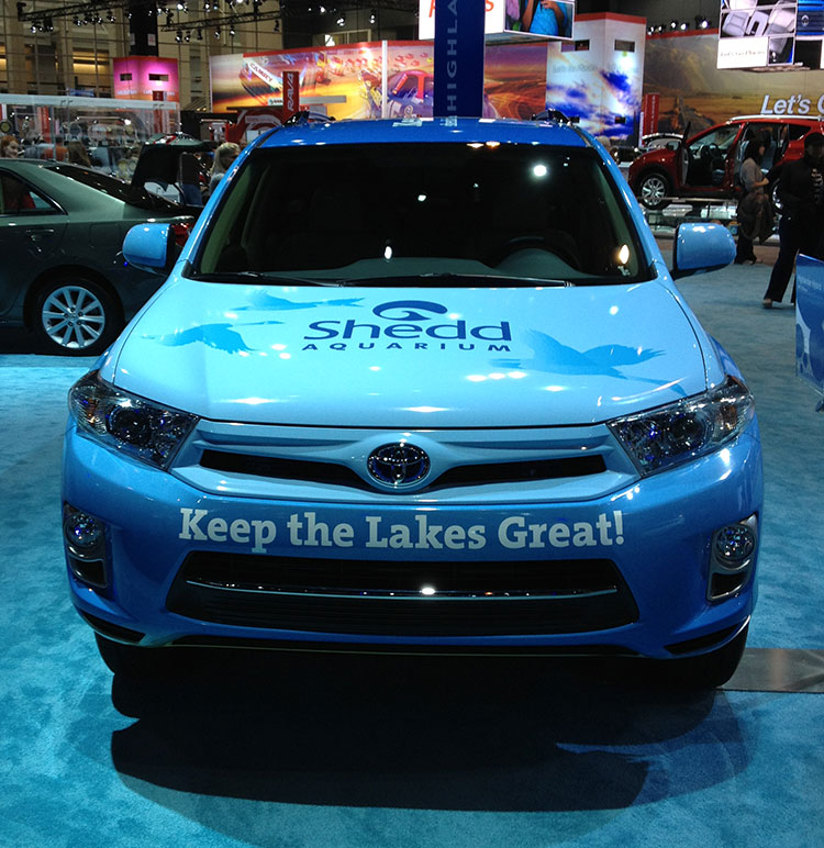 The front of a Toyota SUV, wrapped in light blue and with the message, 'Keep the lakes great!' on the front bumper.