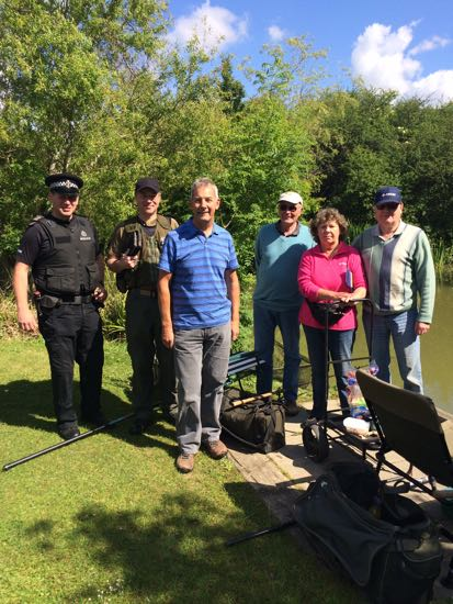 VBS South Downs Area Coordinator Colin Sterling (third from left), PC Keith Buckley of Sussex Police and an Environment Agency fisheries enforcement officer – with anglers reassured by their presence at a venue where drug dealing was suspected.