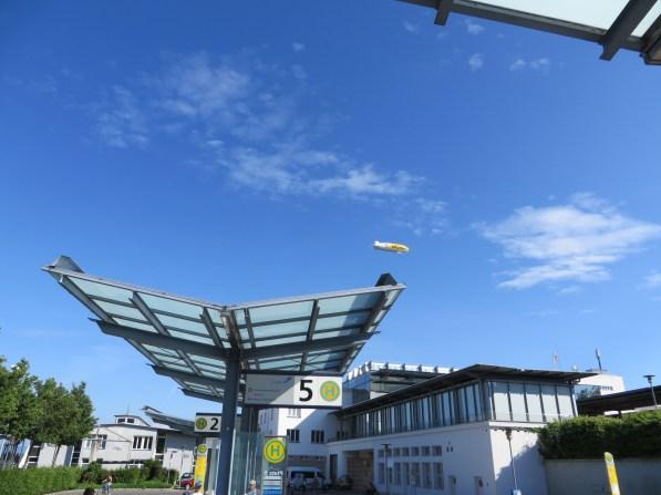 Die Busfahrt startet am Hafenbahnhof: Am Himmel schon der Zeppilin, wer ist wohl schneller am Hangar?