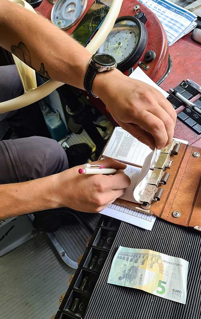 Der Fahrschein wird von Hand herausgeschrieben.