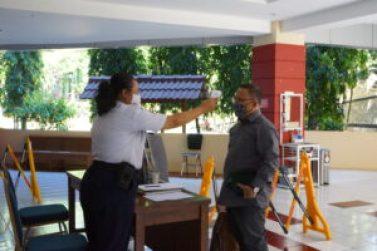 Foto Satpam tengah memeriksa suhu tubuh pengunjung gedung Rektorat