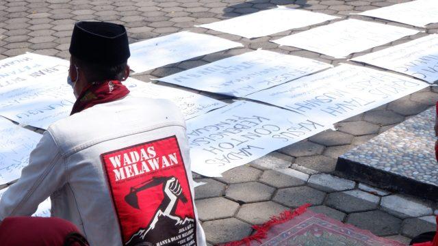 Warga Wadas menunggu di halaman PTUN Semarang dan membawa berbagai atribut poster [BP2M/Adam].