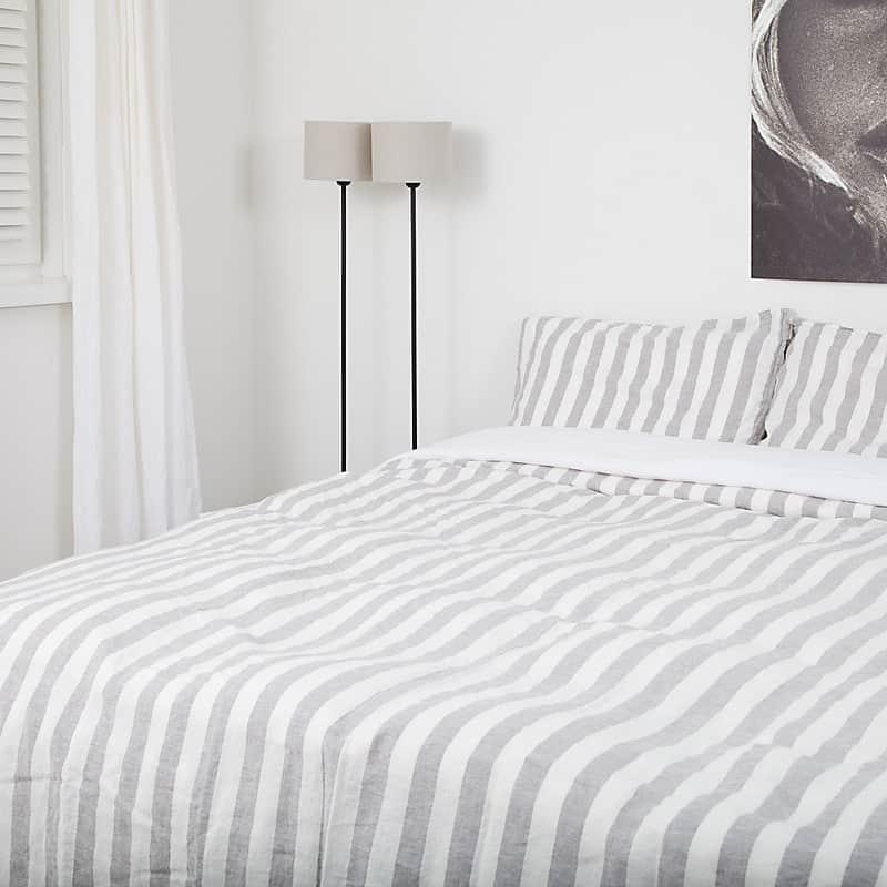 bed met gestreept dekbedovertrek erop in grijs witte strepen
