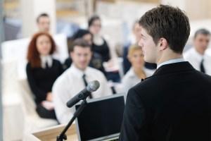 immagine con persona che parla durante una presentazione