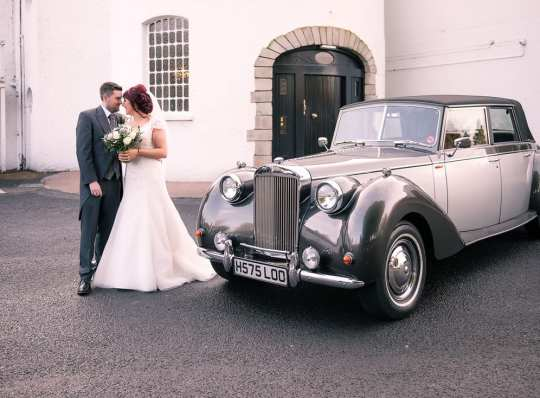 bride and groom by classic limousine