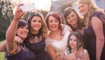 bridal party take a group selfie at wedding
