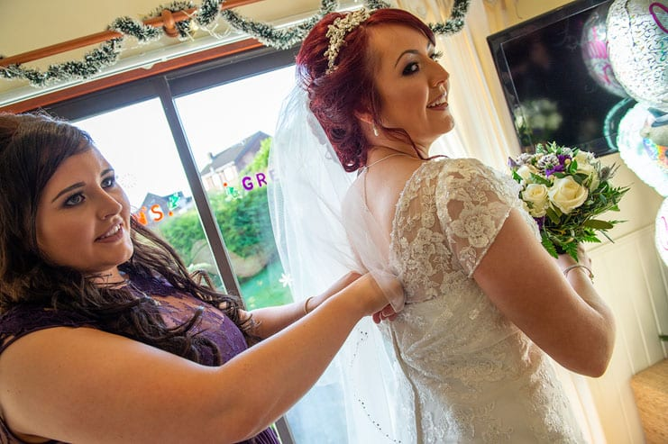 the bride has her dress fastening checked