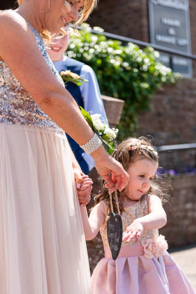 flower girl holds hand out for wedding prop