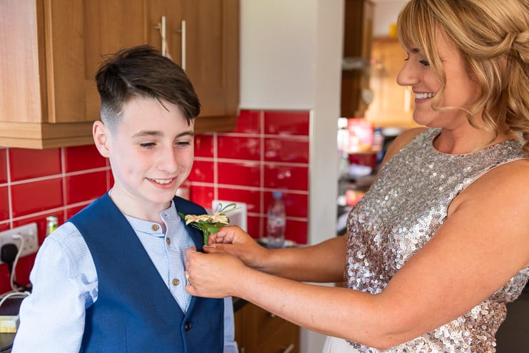 mum helps page boy with button hole flower