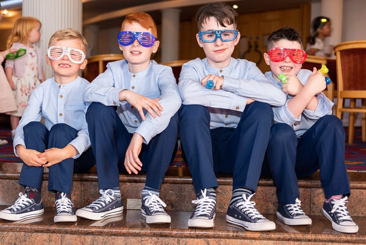 boys posing with fun glasses at reception