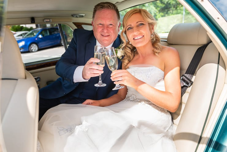 bride and groom enjoy a toast in wedding car