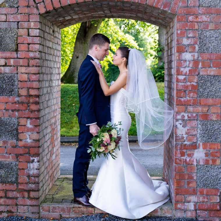 bride and groom pose in arch