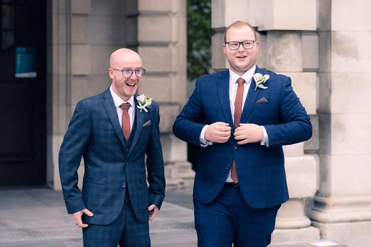 groom and best man laugh when asked to button jackets