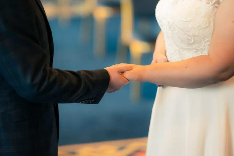 bride and groom hold hands during wedding vows