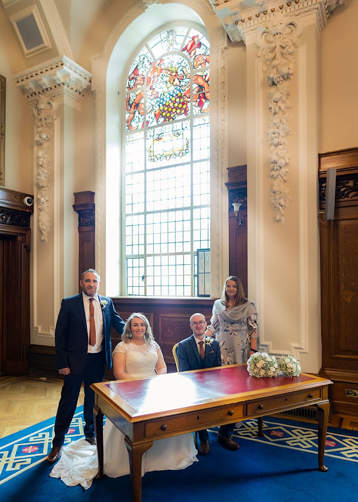family group by large stain glass window at belfast city hall wedding