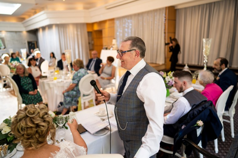 grooms speech with guests in background