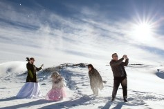 bridal party playing with snow on mountain