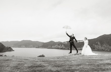 bride and groom having fun by the bay