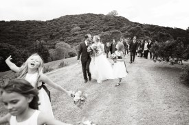 monochrome photo of the bride and groom exiting the ceremony with the flower girls leading the way at Oke Bay north of Auckland