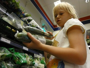 A is picking out the right cucumber at the store