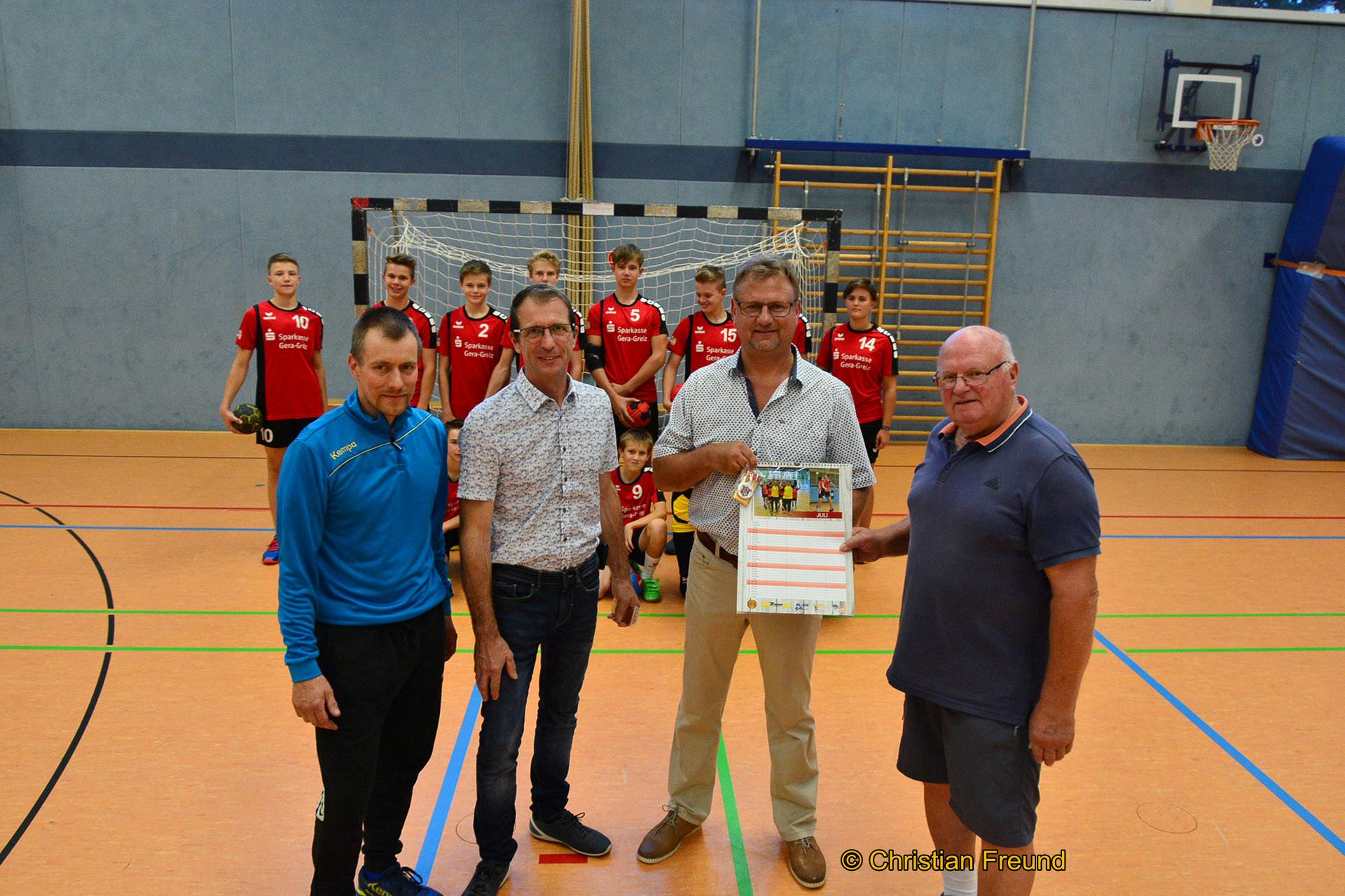 Lions-Vorstandsmitglied Sven Heisig (3.von links) und Jörg Hierold (2. von links) übergeben Trainer Gerwin Bölke (rechts) und Co-Trainer Thomas Peschke die Spende.