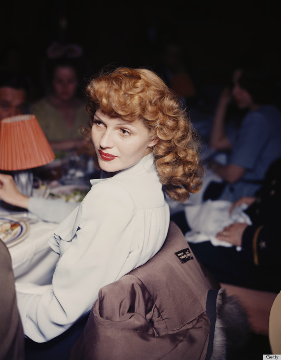 circa 1944: American actor Rita Hayworth (1918 - 1987) turns her head while leaning back in a chair at a dining table in a restaurant. Hayworth wears a white blouse with ruffles. (Photo by Hulton Archive/Getty Images)