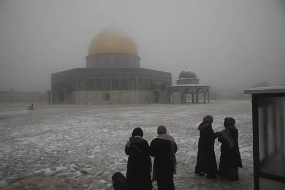 Sejumlah wanita berdiri di dekat Masjid Kubah Batu di kompleks Masjid Al Aqsa pada pagi bersalju di Kota Tua Yerusalem, Kamis (18/2).