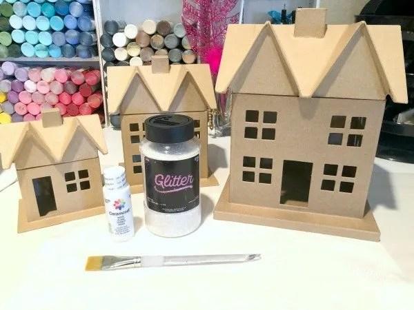 brown paper mâché houses, glitter, paint and paint brush