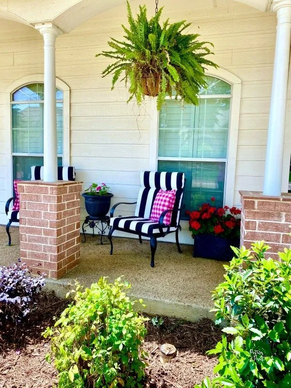 pink pillow, black and white chair, front porch
