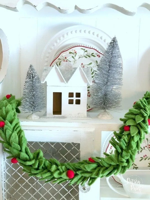 White Christmas houses with glitter snow, silver bottle brush trees and green garland