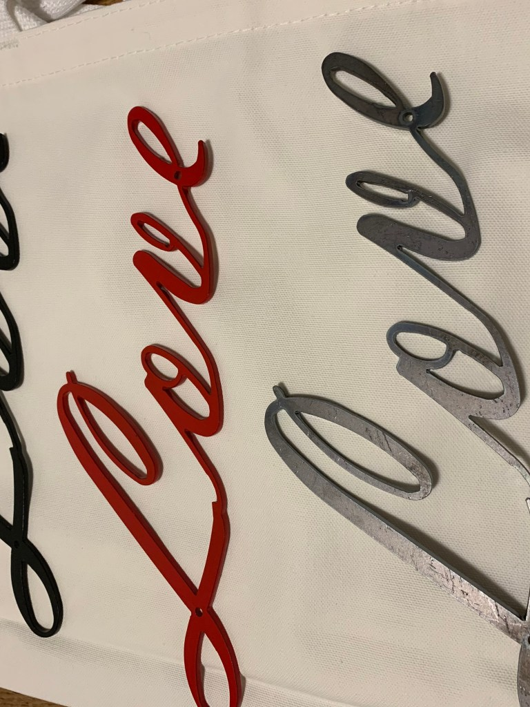 3 metal signs that say love in cursive letters