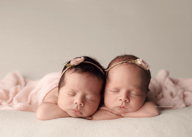 close up of twin newborn girls snuggled together on a cream backdrop san diego