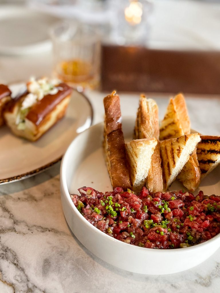 A low deep bowl serves a half-moon of beef tartare peppered with baby chives.  Six substantial triangles of toast are arranged tips up.