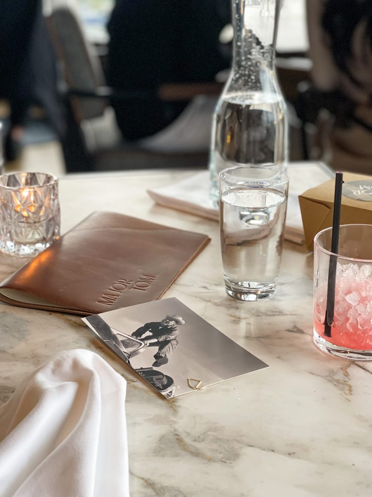 A well enjoyed table is scattered with near-empty glassware, a napkin, and the bill.