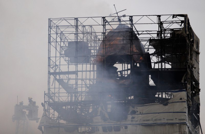 Two firefighters stand in a cherry picker next to the charred clock tower of Pittsboro, N.C.'s historic courthouse on March 25, 2010. The clock tower caught on fire in the afternoon and fell over later that night. Witnesses said that scaffolding and plastic around the tower, which was being renovated, seemed to prevent firefighters from spraying water on it to put out the blaze.