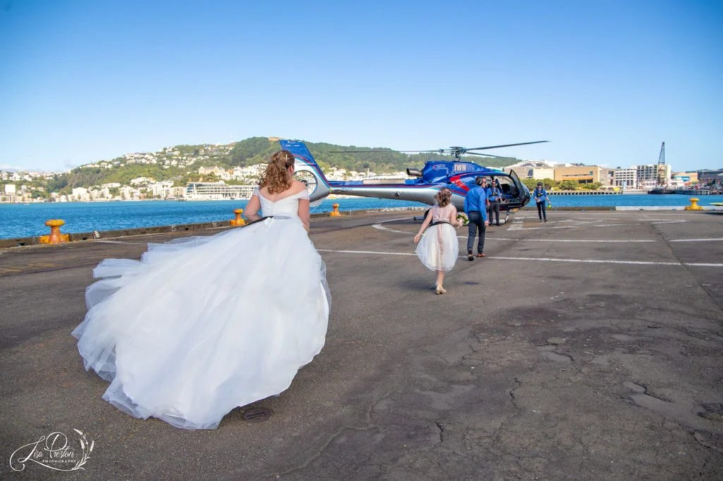 Bride walking to helicopter for flight to wedding