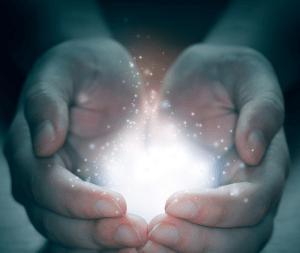 glowing light held in palms
