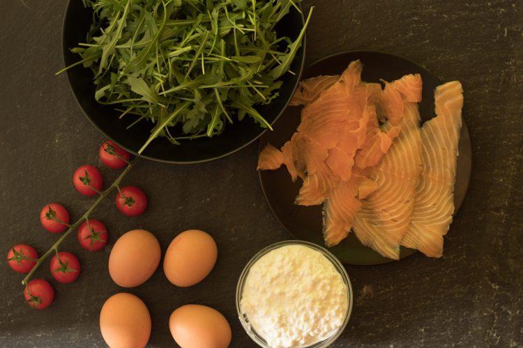 Zutaten für eine leckere, gefüllte Omelettrolle - Räucherlachs, Eier, Rucola, körniger Frischkäse und Tomaten