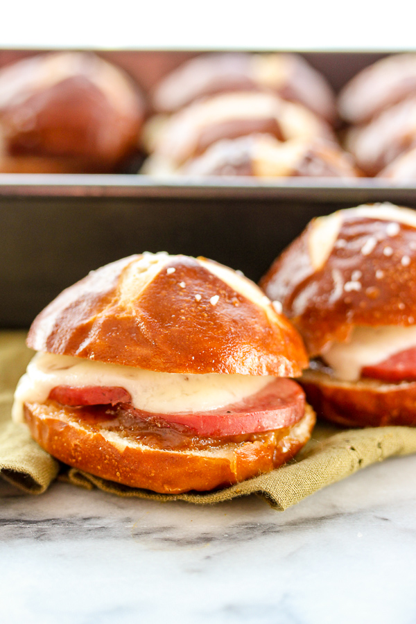 Klement's garlic summer sausage combines with manchego cheese and a homemade Apricot mustard spread to create these irresistible pretzel bun sliders. #klements #linkup