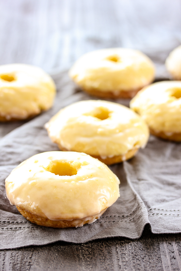 These baked glazed lemon donuts couldn't be easier to make and are bursting with fresh, tangy lemon flavor. They are guaranteed to disappear quickly.